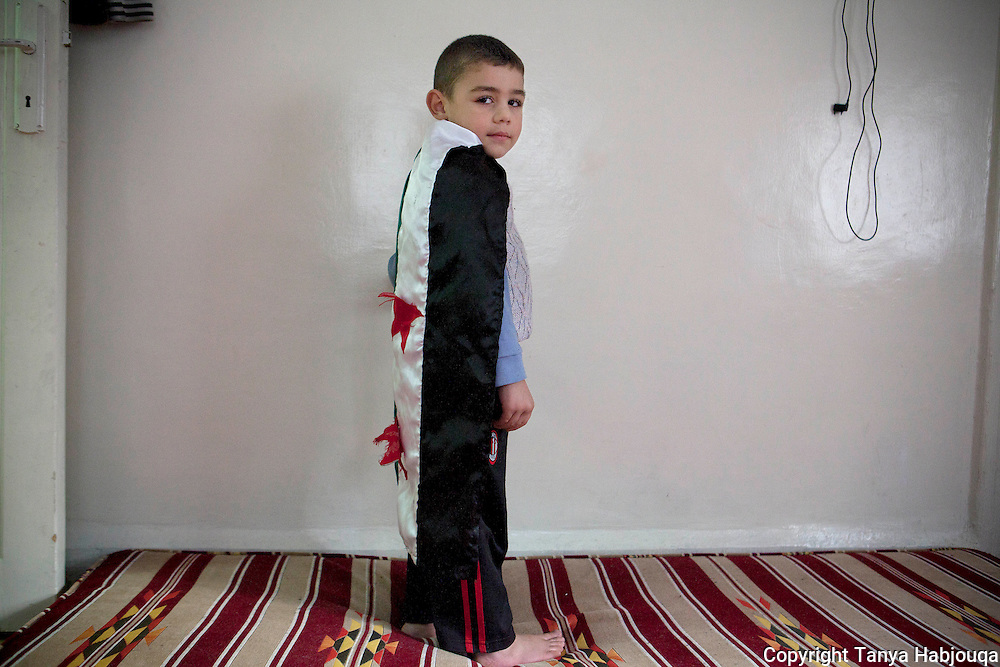 Sufian, 4 years old, and son of torture survivor Abu Khatab. He was small baby on multiple occasions his father was jailed--and did not recognize him on one return home, asking him if he was his father. Living in a sparse home, the few things hanging in the wall include the original Syrian flag previous to Assad regime, which Sufian enjoys playing with.