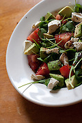 A salad featuring locally grown arugula and tomato, photographed at an angle.