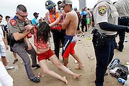 State troopers remove an intoxicated spring breaker off the beach as police try to shut down Coca Cola Beach during Spring Break on South Padre Island. An incident