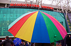 MANCHESTER, ENGLAND - Sunday, January 15, 2017: A rainbow umbrella shields a supporter from the rain outside Old Trafford ahead of the FA Premier League match between Manchester United and Liverpool. (Pic by David Rawcliffe/Propaganda)