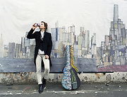 Young woman leaning against wall with guitar case next to her and drinking from a take away cup.