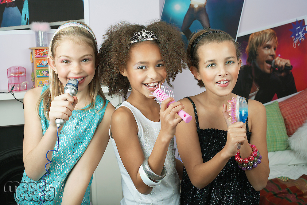 Girls using brushes microphones to sing at a Slumber Party