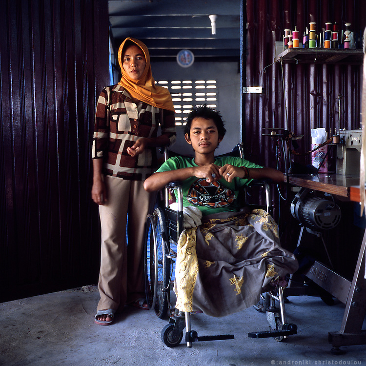 """Rohishamu (19) lost his legs when he was shot three years ago by a guy on a motorbike in a random shooting in Narathiwat. His mother Maresha managed to get them accepted in Rotan Batu village where they could find some peace.  .Rotan Batu, also known informaly as """"Widdows village"""" started functioning in 2004 as a project that was funded and created by Thailand's Queen Sirikit, who donated 20m baht ($514,000) of her own money to purchase the land on which the village is now located. Its purpose is to give shelter and work to mainly Muslim widows who lost their husbands during the insurgency in the south of Thailand. They now live there about 450 people, the widows together with other members of their families. The village is self sufficient as there is enough farm-land where they produce the vegetables and fruit for themselves and sell the extra production in local markets. They also create handcrafts which are sold as souvenirs in other parts of Thailand giving them some extra income. The village is considered quite safe but it is guarded by solders 24 h a day to make sure no attack happens there."""