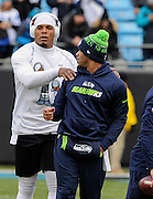 Carolina Panthers quarterback Cam Newton, left, speaks with Seattle Seahawks quarterback Russell Wilson before the first half of an NFL divisional playoff football game between the Carolina Panthers and the Seattle Seahawks, Sunday, Jan. 17, 2016, in Charlotte, N.C. (AP Photo/Mike McCarn)