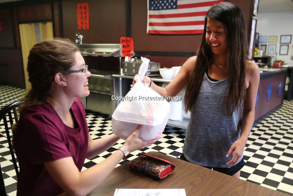 HiuLaam Chow hands a takeout oder to customer Deanna Miller, of Blue Springs. Hong Kong Buffet serves authentic Asian cuisine and has offers a lunch buffet along with take out orders.