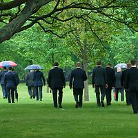 Men in smart city suits walking in Hyde Park, London