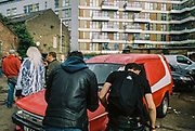 Men milling around outside at DJ Gordie's 71st birthday party, Hackney Wick, London 2017