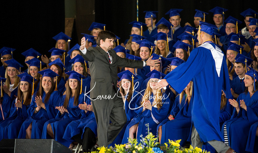 Social Studies Teacher Corey Nazer extends a hug to Vice President Malcolm Benavides after his introduction as the Keynote Speaker during Gilford High School's graduation ceremony at Meadowbrook Pavilion Sunday morning.  (Karen Bobotas/for the Laconia Daily Sun)