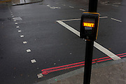 A 'Wait' warning to pedestrians, illuminated on a road crossing sign in central London, England.