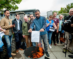 Pictured: Asylum seeker Rahman Shah burns his eviction letter from SERCO.<br /> <br /> Protesters gathered outside the main Home Office building in Glasgow to protest at private company SERCO's attempts to evict failed asylum seekers from their homes.<br /> <br /> &copy; Dave Johnston / EEm