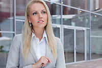 Thoughtful businesswoman looking away against office building