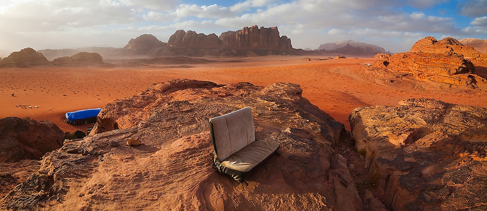 A retired Jeep seat at Bedouin Meditation Camp with a vast sunset view over the red sand desert and sandstone cliffs of Wadi Rum, Jordan.