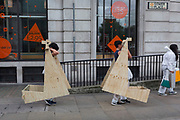 Architecture students carry awkward plywood cut-out shapes as part of their course at University College London (UCL), on 3rd August 2017, in London, England.