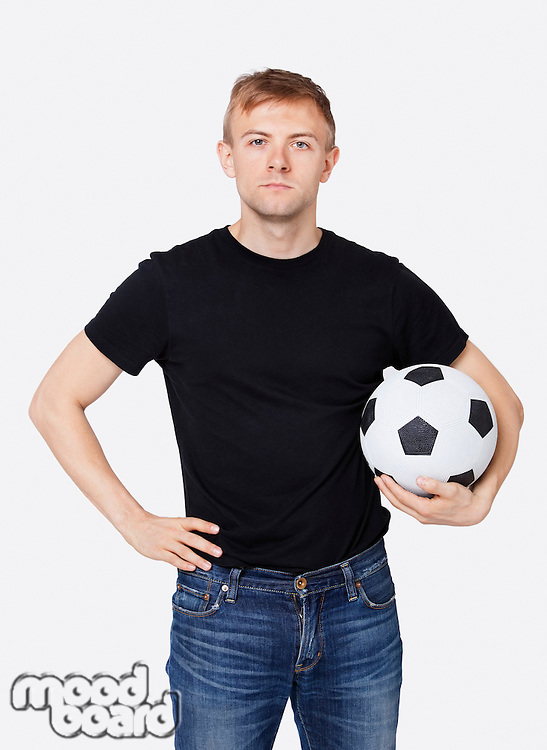 Portrait of a young handsome man in casual wear holding soccer ball over white background