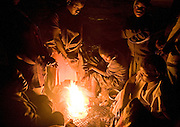 A group of street people gather at one of their 'bases' on a wasteland in Harare, Zimbabwe. They have a fire going to keep warm in the cold nights burning anything they can find including plastic and rubber that give off bad fumes.