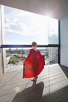 Rear view of boy in superhero costume at home