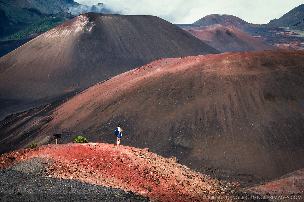 A day hiker overlooks the grandeur of the cinder cones in the seven mile long and two mile wide and 2,600 feet deep Haleakalā Crater in Haleakalā National Park on the island of Maui, Hawaii. The female hiker in this photo is standing atop the Ka Lu'u o ka 'O'o cinder cone looking out towards (front to rear) the cinder cones of Kama'oli'i, Pu'u o Maui and Pu'u Maile. In the far distance is the Kaupo Gap. The Haleakalā Volcano of east Maui is considered dormant, having last erupted sometime between 1480 and 1600 AD. The 33,265 acre park consists of the Summit District and the coastal Kipahulu District. Haleakalā National Park is known for it volcanic features, cinder cones and clear night skies for star gazing. It is believed that there are more endangered species living in Haleakalā National Park than any other national park, including the Haleakalā Silversword plant.