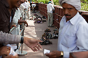 Visitors are collecting their shoes, prohibited without proper shoe-covers inside the Taj Mahal main complex, in Agra.