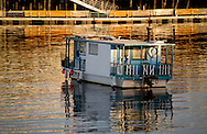 A quaint houseboat on calm Monterey harbor waters at illuminated by golden sunset light