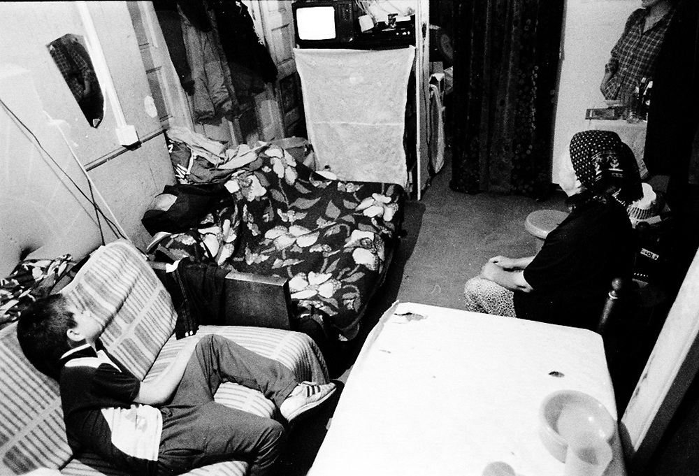 Anja, Dejan and their grand-mother inside their cubicle...The Krstic family left Kosovo after they were threatened to have their house burnt. They are sharing a warehouse with another 20 families where only thin partitions divide one room from the other. Anja and Dejan go to the local school but feel their only friends are in the camp. They feel rejected by the other children at school. They are seen as being different even if they are Serbs. ...During the summer1999, over 245,000 Serbs and Roms fled to Serbia and Montenegro from or within Kosovo in fear of reprisals from the majority Albanian population, after NATO air strikes had forced the withdrawal of Yugoslav. In 2003, less than 2% of them had returned and a large number of these internally displaced persons (IDPs) were still living in camps in very difficult conditions..In addition, around 5,000 IDPs, mainly of Roma ethnicity, are living in unrecognized collective centres, makeshift huts, corrugated metal containers and other substandard shelters. .This work was meant to look at how the life of children and young adults is affected by the fact that they are IDPs. I asked myself more specifically what would be different for these children/young adults from the 'normal' people of their age as far as education, health, social life, family, 'love' life and leisure are concerned. ...Anja, Dejan et leur grand-mère dans leur 'cabine'...La famille Krstic a quitté le Kosovo après qu'on les ait menacé de brûler leur maison. Ils partagent un entrepôt avec 20 autres familles séparées entre elles par des cloisons très fines.  Anja et Dejan vont à l'école locale mais se sentent rejetées par leurs compagnons de classe. Ils sont vus comme étant 'différents' même s'ils sont serbes...Pendant l'été 1999, plus de 245 000 serbes et roms ont fuit le Kosovo pour chercher refuge en Serbie ou au Montenegro, par peur de représailles de la part de la majorité de la population albanaise après que les forces de l'OTAN aient forcé l'armée