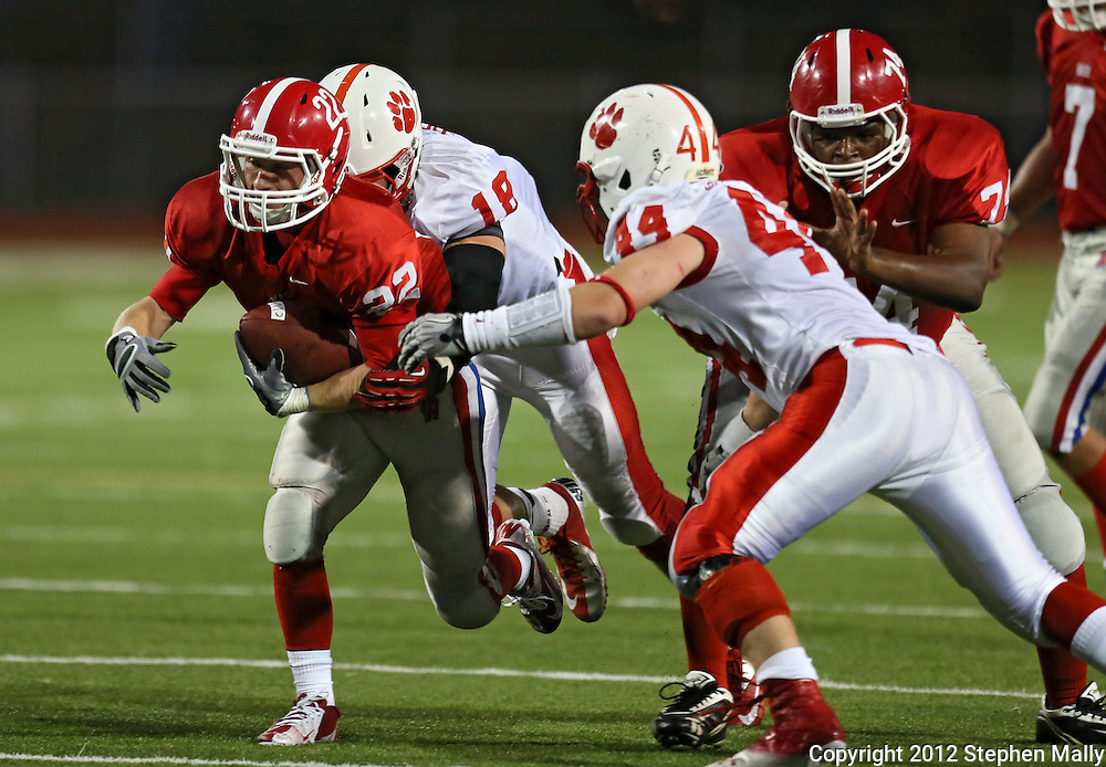 Washington's Mitch Bredeson (22) is brought down by Cedar Falls' Ike Boettger (18) as Rylee Willett (44) tries to get around Washington's Kaine Cooks (74) during the game between Cedar Falls and Cedar Rapids Washington at Kingston Stadium in Cedar Rapids on Friday, September 7, 2012.
