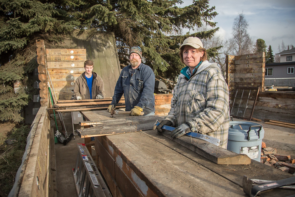 """We've been working on this house since Christmas…it's our plan to reconstruct it in Homer.""  Scott Gorder and his girlfriend, Barbara Keller, and his son, Colten, disassemble a historic log structure at the corners of 15th and H Streets."