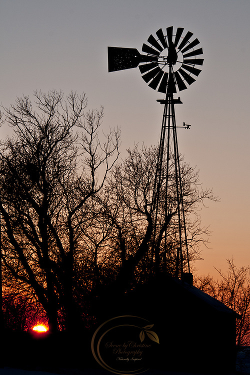 An old windmill stands silhouetted against a setting sun.