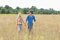 Young couple holding hands while walking through field