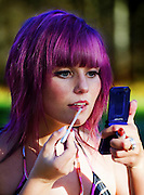 Young woman with purple hair applies make up
