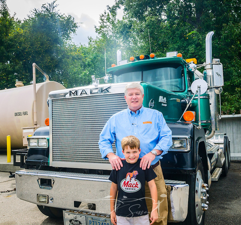 Pat Barber stands in front of an antique Mack truck with his son, James Barber, at Superior Transportation, Sept. 30, 2015, in North Charleston, South Carolina. Pat Barber started the company in 1998. James, 6, is already showing a big interest in the company and its Mack trucks, and Barber says he hopes he will follow in his footsteps and carry on the family legacy.  (Photo by Carmen K. Sisson/Cloudybright)