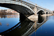 """Low angle view of Enrique Estevan Bridge across the River Tormes, Salamanca, Spain, pictured on December 18, 2010 in the afternoon. The elaborate iron spans are clearly reflected in the river by the winter sunshine. Salamanca, an important Spanish University city, is known as La Ciudad Dorada (""""The golden city"""") because of the unique golden colour of its Renaissance sandstone buildings. Founded in 1218 its University is still one of the most important in Spain. Around it the Old Town is a UNESCO World Heritage Site. Picture by Manuel Cohen"""