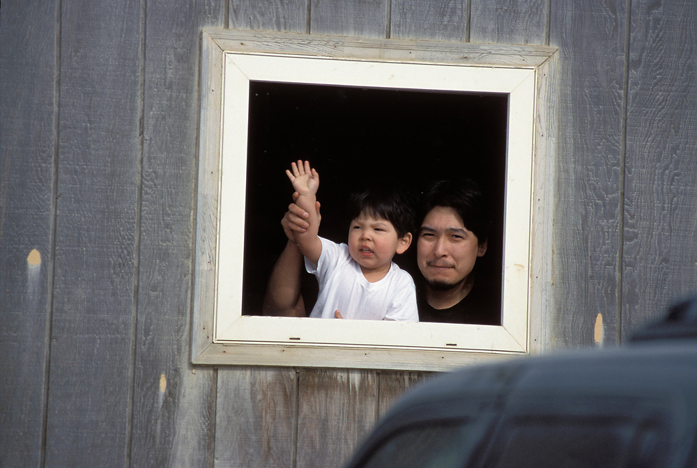 Barrow, Alaska. Father and son wave from a window in Barrow, Alaska.