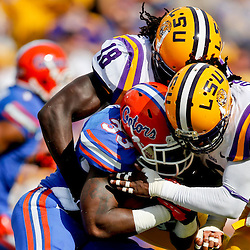 Oct 12, 2013; Baton Rouge, LA, USA; Florida Gators running back Mack Brown (33) is tackled by LSU Tigers safety Craig Loston (6) and linebacker Lamin Barrow (18) during the first half of a game at Tiger Stadium. Mandatory Credit: Derick E. Hingle-USA TODAY Sports