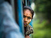 26 OCTOBER 2015 - YANGON, MYANMAR: A woman leans out the window on the Yangon Circular Train. The Yangon Circular Railway is the local commuter rail network that serves the Yangon metropolitan area. Operated by Myanmar Railways, the 45.9-kilometre (28.5 mi) 39-station loop system connects satellite towns and suburban areas to the city. The railway has about 200 coaches, runs 20 times daily and sells 100,000 to 150,000 tickets daily. The loop, which takes about three hours to complete, is a popular for tourists to see a cross section of life in Yangon. The trains run from 3:45 am to 10:15 pm daily. The cost of a ticket for a distance of 15 miles is ten kyats (~nine US cents), and for over 15 miles is twenty kyats (~18 US cents).     PHOTO BY JACK KURTZ