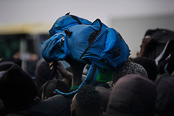 © Licensed to London News Pictures. 24/10/2016. Calais, France. A bag is passed over peoples heads as migrants queue to be processed during the evacuation and demolition of the migrant camp in Calais, known as the 'Jungle'. French authorities have given an eviction order to thousands of refugees and migrants living at the makeshift living area of the French coast. Photo credit: Ben Cawthra/LNP