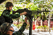 "20 MAY 2104 - BANGKOK, THAILAND: Thai soldiers with a machine gun at a checkpoint on Rama I Road in Bangkok after the Thai army declared martial law. The army declared martial law throughout Thailand in response to growing political tensions between anti-government protests led by Suthep Thaugsuban and pro-government protests led by the ""Red Shirts"" who support ousted Prime Minister Yingluck Shinawatra. Despite the declaration of martial law, daily life went on in Bangkok in a normal fashion. There were small isolated protests against martial law, which some Thais called a coup, but there was no violence.   PHOTO BY JACK KURTZ"
