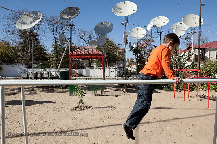 A boy plays outside his home in central Ashgabat. Satellite dishes abound in Turkmenistan, providing residents access to Russian and Turkish news. Since the state-controlled Russian media's apparent interference in Kyrgyzstan and Belarus this year, observers in Ashgabat suggest the satellites give the Kremlin a quiet lever of power over the country.