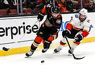 Anaheim Ducks forward Andrew Cogliano (L) and Calgary Flames defenseman TJ Brodie vie for the puck during a 2017-2018 NHL hockey game in Anaheim, California, the United States, on Oct. 9, 2017.  Calgary Flames won 2-0. (Xinhua/Zhao Hanrong)