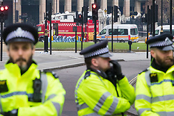 Westminster, London, March 23rd 2017. Police officers man a cordon outside Westminster Abbey while in the background officers in forensic overalls conduct a fingertip search on Parliament Square as investigations continue following Tuesday's terrorist attack on Westminster Bridge and in the grounds of Parliament, in which four people and their attacker were killed with over 40 injured.