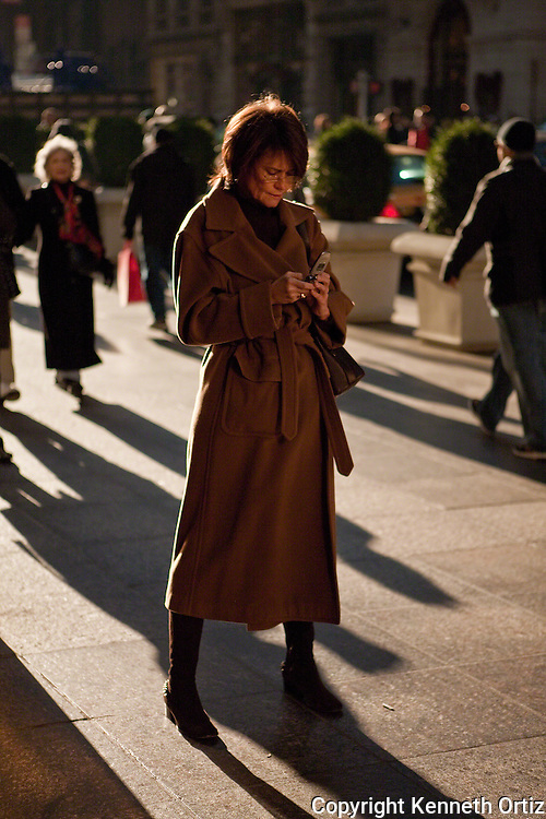 A woman dialing a number on her cell phone on 5th Avenue in Manhattan while backlit by the sun.