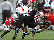 MORNING JOURNAL/DAVID RICHARD.Ohio State defenders Anderson Russell, left, and James Laurinaitis bring down running back Garrett Wolfe and center Eddie Adamski yesterday in the fourth quarter.