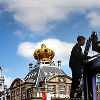 Nederland, Amsterdam , 28 april 2013.<br /> Voorbereidingen en opbouw van de media op de Dam Koningsdag 30 april.<br /> De NOS heeft een glazen huis op de Dam geinstalleerd van waaruit verslag zal worden gedaan tijdens de Kroningsdag.<br /> De nodige voorbereidingen worden getroffen. Kabels worden aangebracht, perstribunes opgebouwd etc.<br /> Op de foto: Er wordt gewerkt aan het glazen huis van de NOS. Daarboven hangt een camera die via een rail over de hele Dam kan glijden.<br /> Preparation and build up the media at the Dam in Amsterdam for King's Day, April 30th.<br /> The NOS installed a glass house at the Dam from which they will be broadcast at the King's Day.<br /> <br /> Foto:Jean-Pierre Jans