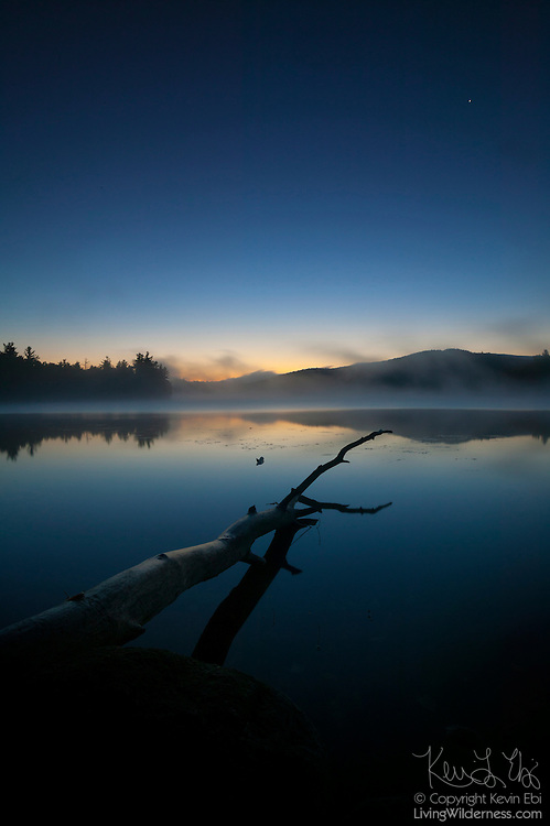 Mountains and trees reflect onto the still waters of Franklin Falls Pond in the Adirondack Mountains of New York just before sunrise. A star is visible in the right corner of the image.