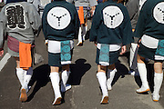 back view of men walking in traditional Japanese Happi clothing