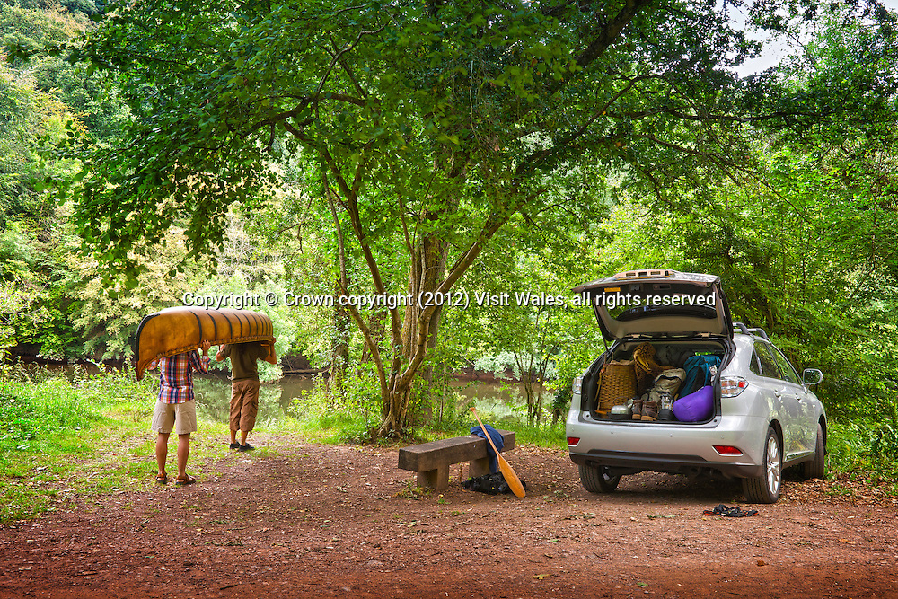 Man unloading wooden canoe from car<br /> Canoeing<br /> Activities and Sports