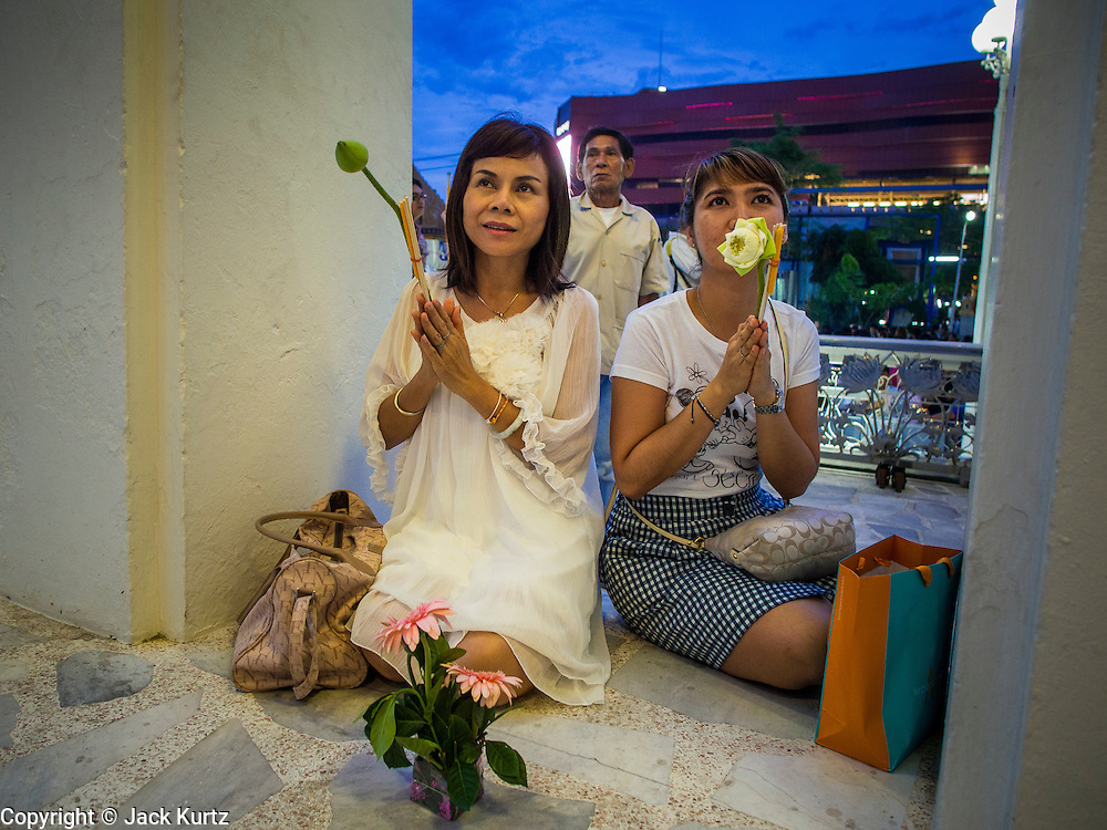 """13 MAY 2013 - BANGKOK, THAILAND: Women pray during Vesak ceremonies at Wat That Thong in Bangkok. Vesak, called Wisakha Bucha in Thailand, is one of the most important Buddhist holy days celebrated in Thailand. Sometimes called """"Buddha's Birthday"""", it actually marks the birth, enlightenment (nirvana), and death (Parinirvana) of Gautama Buddha in the Theravada or southern tradition. It is also celebrated in Cambodia, Laos, Myanmar, Sri Lanka and other countries where Theravada Buddhism is the dominant form of Buddhism.     PHOTO BY JACK KURTZ"""