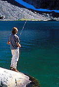 Young hiker fishing on the shore of Minaret Lake, Ansel Adams Wilderness, Sierra Nevada Mountains, California
