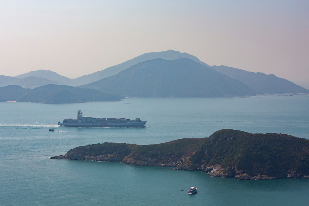 A large cargo ship crossing the Aberdeen Channel in Hong Kong on a hazy day. To the left is Oceans Park, and the island in the background is Lamma Island. (photo by Andrew Aitchison / In pictures via Getty Images)