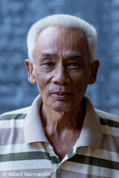Portrait of market caretaker in front of blue wall, Hpa-an