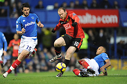 Wayne Rooney of Manchester Unite jumps over the tackle of Younes Kaboul (R-Portsmouth) as Marc Wilson (Portsmouth) looks on. Portsmouth v Manchester United (1-4), Barclays Premier League Fratton Park, Portsmouth, 28th November 2009.